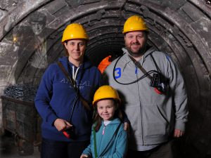 George, Karen and Olivia with hard hats and safety lamps, there is a ghost of an old miner in the background