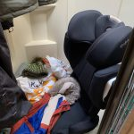 The bottom of the shower, with a car seat, coats and various other things in there