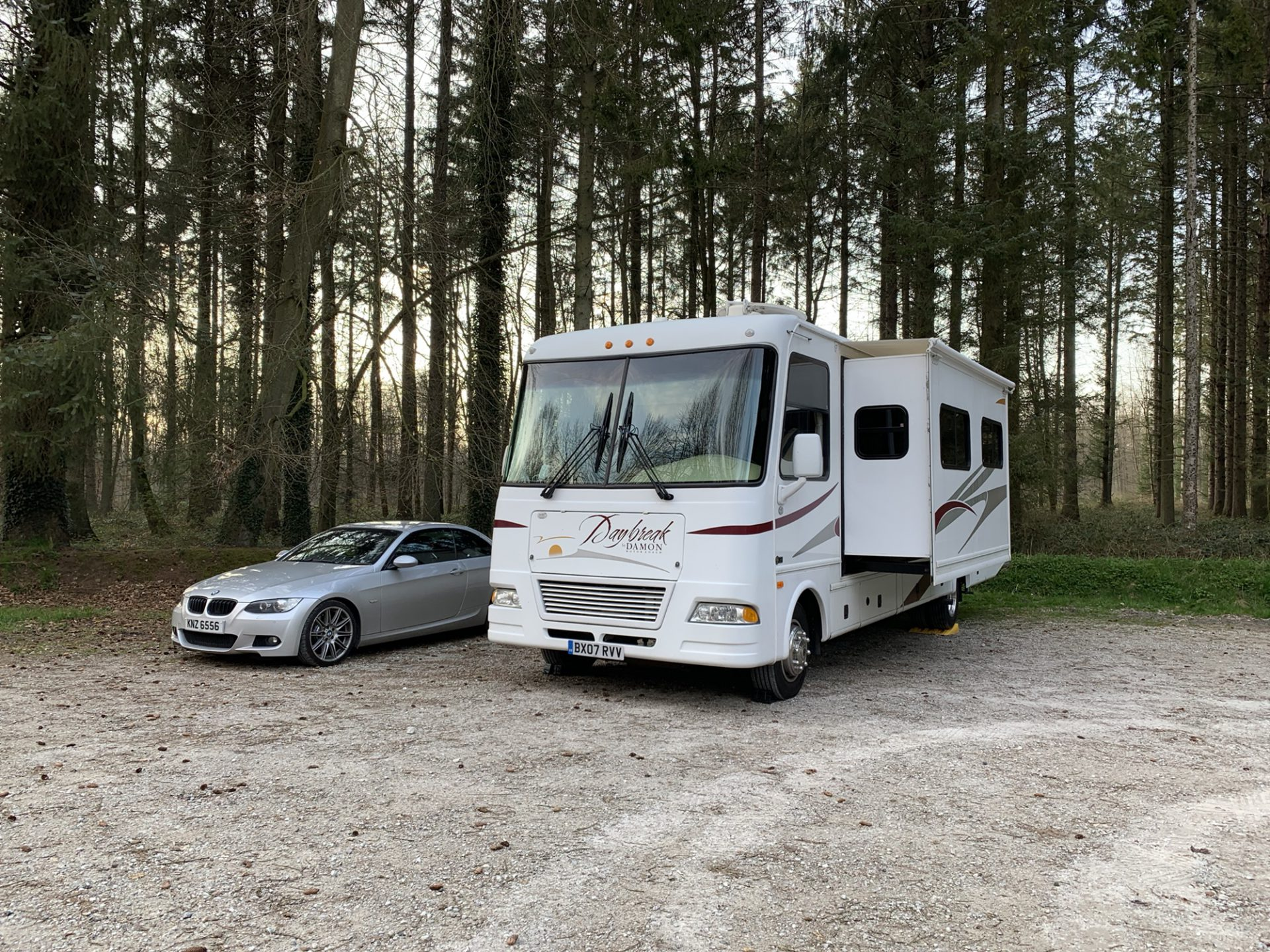 Our RV and our BMW parked in a gravel car park