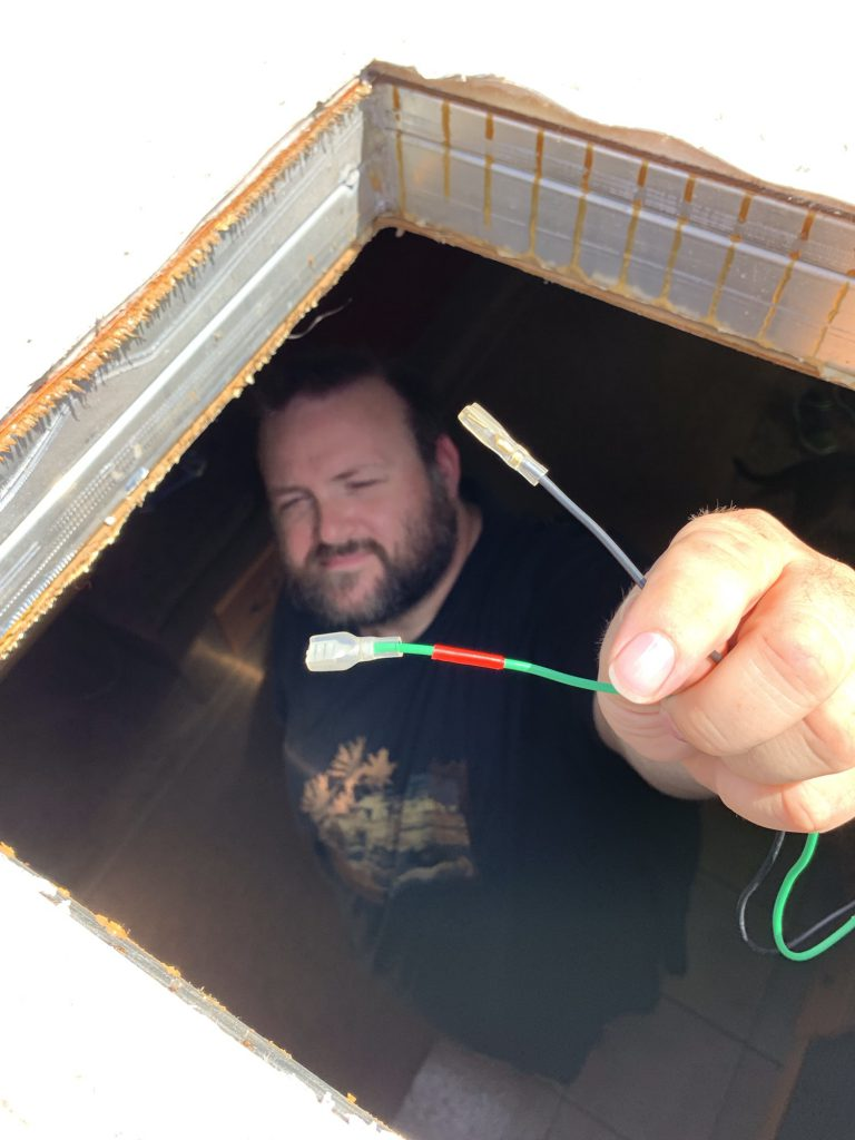 George visible through the roof hole, holding two wires with ends ready for the MaxxFan