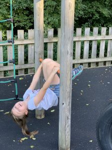 Olivia hangs upside down from some play equipment. Her knees are tucked over a bar which she also hangs on to with her hands