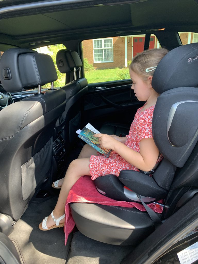 Olivia reads in the back of the X5, the door is open but she doesn't want to get out